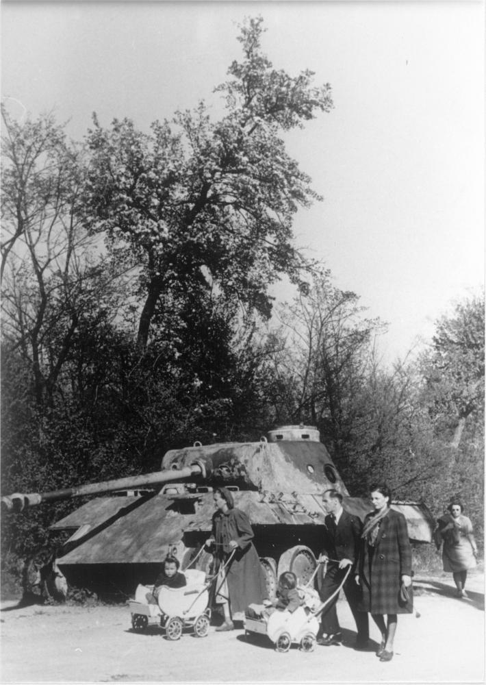 Der Fotograf inszeniert hier die Gleichzeitigkeit von Gewalt und Alltag. Die Kinderwagen neben dem Panzer sind aber auch Symbole für die Überwindung des Kriegs und den Neubeginn.