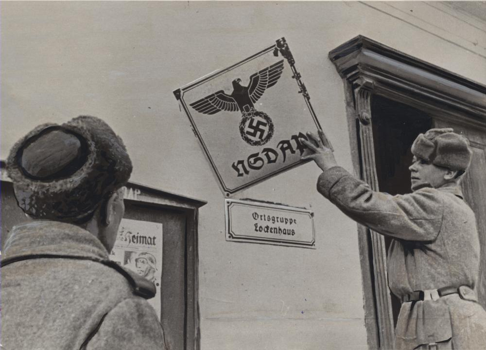 """Die Beschriftung des Fotos zeigt, wie dieses für die sowjetische Presse gedeutet wurde: """"Herunter mit dem verhaßten Zeichen des Kriegs und der Sklaverei! Die symbolische Geste eines einfachen sowjetischen Soldaten."""""""