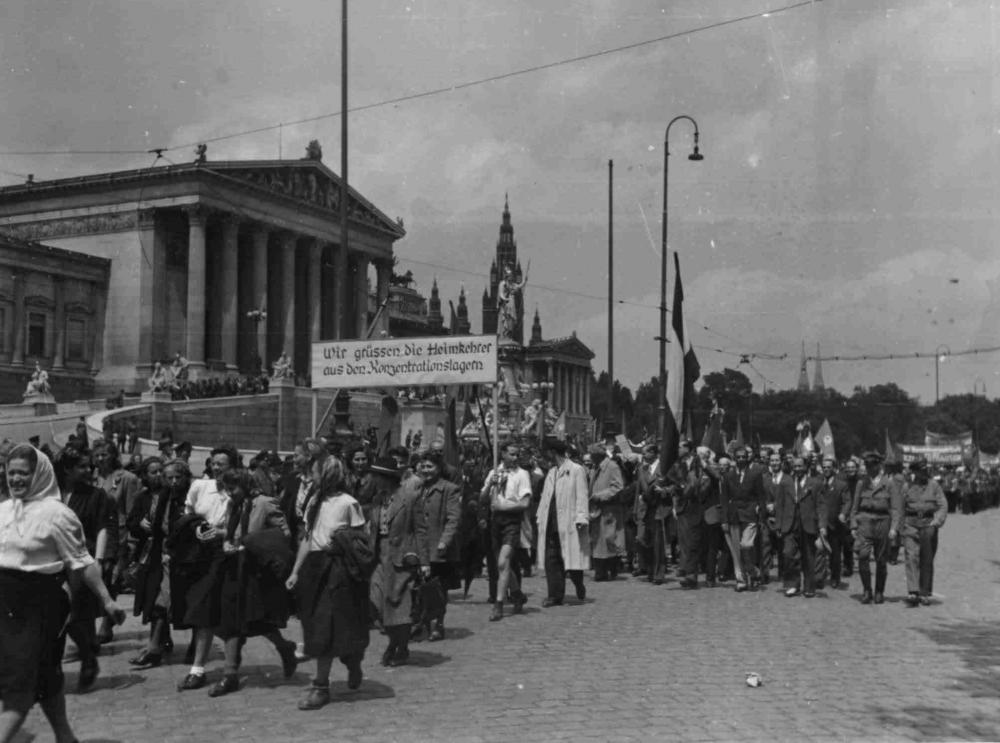 """Aufmärsche sollten nach der Befreiung den NS-Massenveranstaltungen ein starkes Zeichen entgegensetzen. Für einige Monate prägte der Antifaschismus die Öffentlichkeit, wie etwa hier am """"Volkssolidaritätstag"""", der vor allem von und für ehemalige politische Häftlinge organisiert wurde. Die Gruppen waren Überlebende einzelner Konzentrationslager, österreichische Soldaten in den Reihen der Alliierten und eine große Gruppe von Hinterbliebenen der Ermordeten."""
