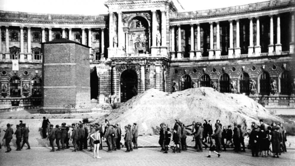 Österreichische Wehrmachtssoldaten, die sich in der Kriegsgefangenschaft freiwillig zum Kampf mit den Alliierten gemeldet hatten, marschieren am zerstörten Heldenplatz ein – im Hintergrund das noch vermauerte Prinz-Eugen-Denkmal und der rechts außen beschädigte Altan der Neuen Burg.