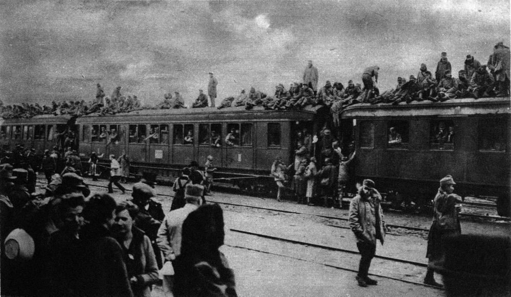 Diese Schwarz-Weiß-Fotografie zeigt große Massen an Soldaten in und um einen Zug. Einige befinden sich sogar auf den Waggons des Zuges.